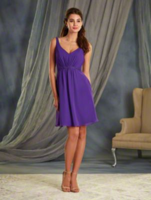 A Cocktail Length, A-Line Style, Short Bridesmaid Dress With A V-Shaped Neckline And Sheer Back Straps Accented with Lace Motifs.