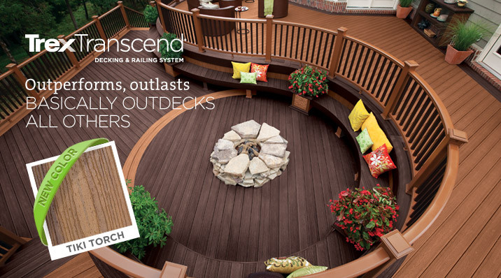 Trex Transcend eco-friendly composite decking and railing in rich earth tones on a luxurious deck filled with curves, built-in seating, plants and a firepit.