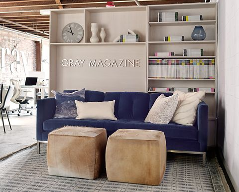 GRAY magazine's modern reception area has a luxury blue velvet Sabine sofa with Lind square cowhide ottomans. Keaton bookcases serve as a room divider and helpful storage.
