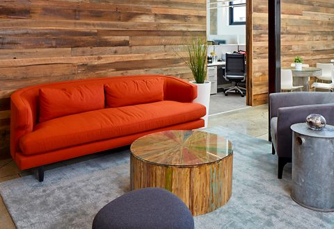 The office reception area seating includes a red custom sofa from Room & Board.
