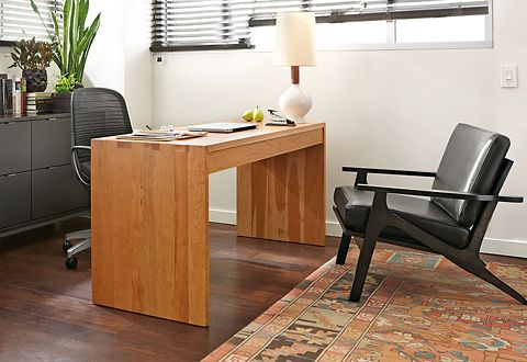 This executive office features a solid cherry Rowan desk with a Luce office chair. Black accents, like the Copenhagen file storage and mid-century modern Sanna guest chair give this private office a sophisticated feel, while a traditional rug adds softness underfoot and dampens office noise.