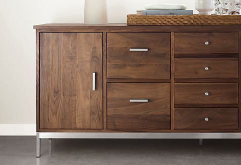 A Linear storage cabinet in walnut with modern stainless hardware holds files and office supplies.
