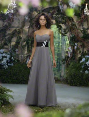 An Alluring Bridesmaid Standing In A Floor Length, Gray Disney Bridesmaid Dress With A Black Satin Cummerbund And Embroidered Lace Accents