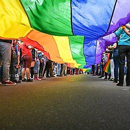 People holding rainbow pride flag