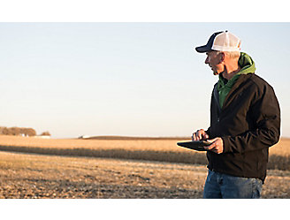 Man with tablet in harvested corn field