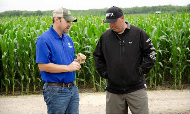 Pioneer Territory Manager Ryan Harms sharing crop management information with a S.A.V.E. participant.
