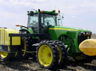 John Deere tractor equipped with tanks for liquid starter application at planting.