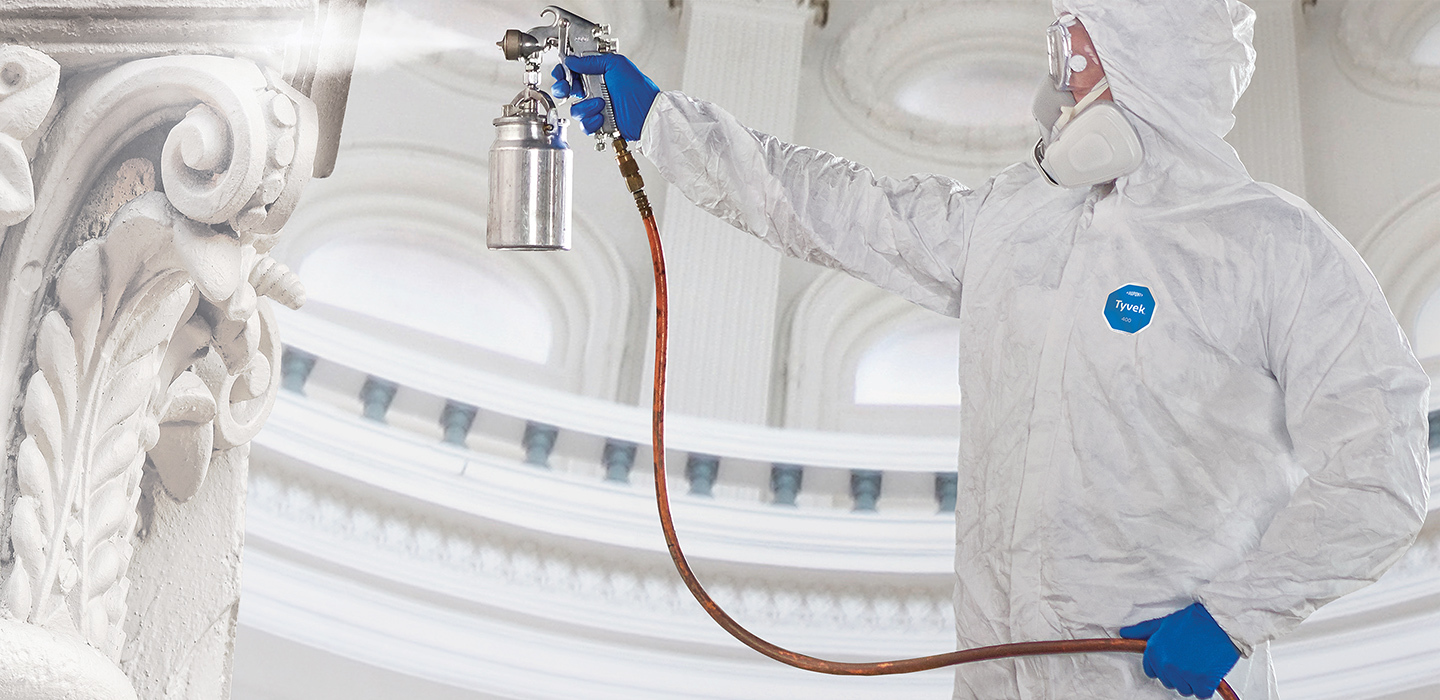 Painter in protective suit using commercial sprayer.