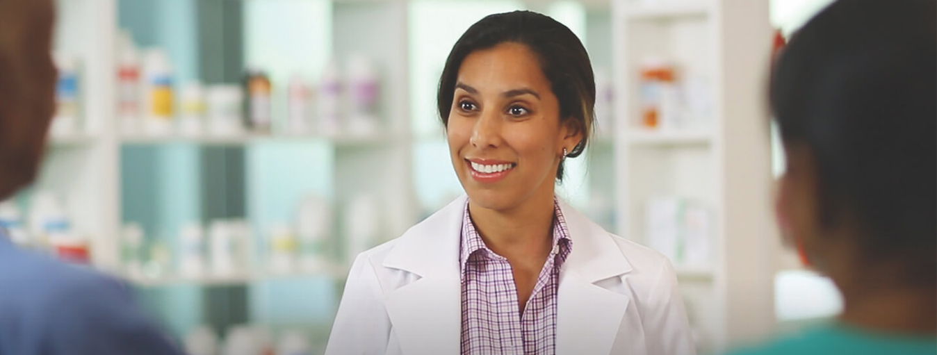 Pharmaceutical technician smiling at two customers.