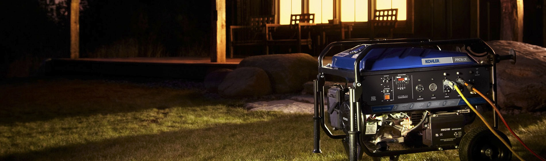 House at night with lights on and KOHLER generator