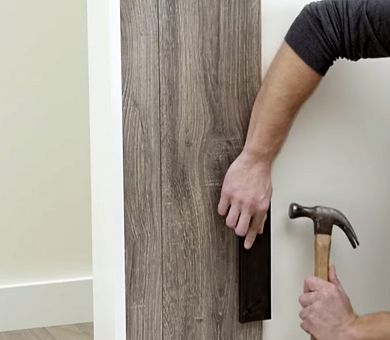 Laminate Wood Planks Being Installed Vertically On A Wall