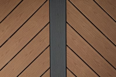 Close up of the wood grain detail of Trex Enhance composite decking in Beach Dune brown and Clam Shell grey