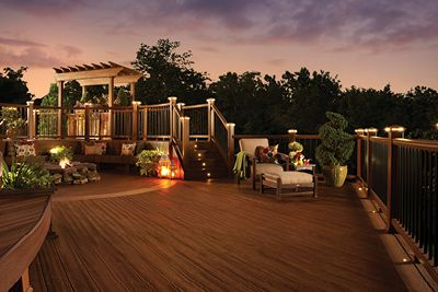 Trex backyard lighting warmly illuminates a composite deck at night