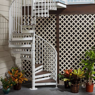 Trex metal spiral stairs in white powder-coated aluminum provides a space-saving solution to connect the deck to the yard