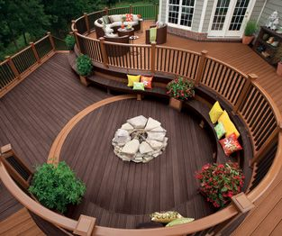 Trex Transcend circular composite decking and railing in Tree House medium brown and Vintage Lantern dark brown create an outdoor oasis with plenty of seating
