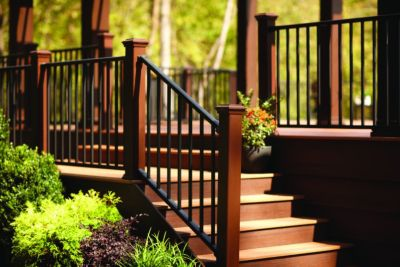 Trex Reveal aluminium deck rail in Charcoal Black with Trex rail posts in dark brown provides an elegant entrance to an outdoor space.