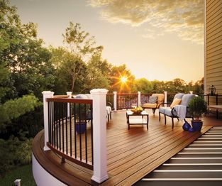 La charpente en acier Trex Elevations supporte un patio composite substitut de bois Trex Transcend au coucher du soleil