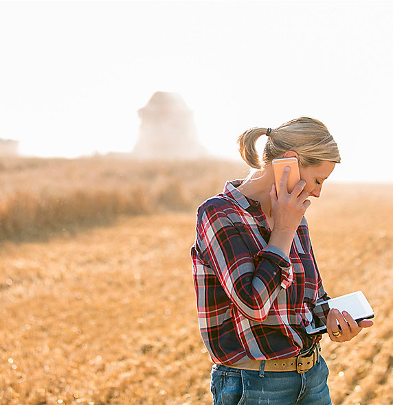 Woman with phone and tablet in field