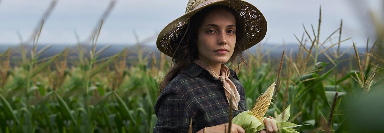 жена фермер с царевица в ръка