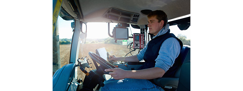 Young man drives tractor