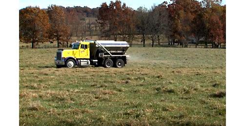 Truck applies impregnated fertilizer to field.