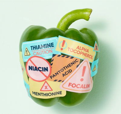 A green pepper with stickers on it.