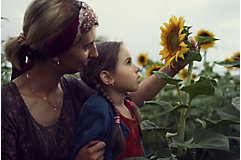 Mother and daughter inspecting sunflower