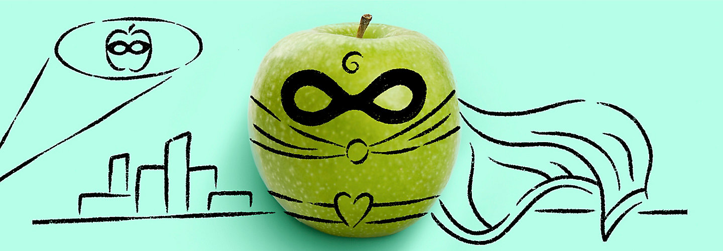 An apple with a stencil drawing over it that depicts the apple as a superhero with a mask and cape.