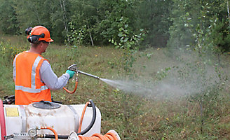Worker spraying with drift