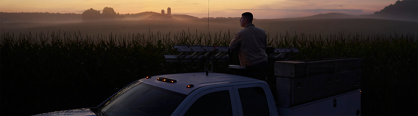 Man standing in truck during sunset
