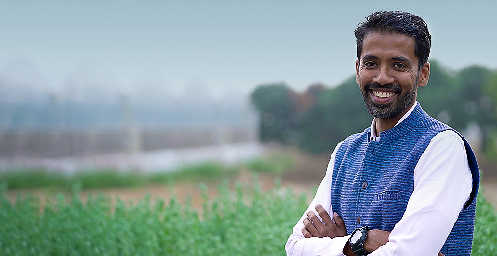 Photo of Corteva data scientist Praveen Pankajakshan standing in a field. Photo taken at Cortevaâ  s research center in Hyderbad, India.