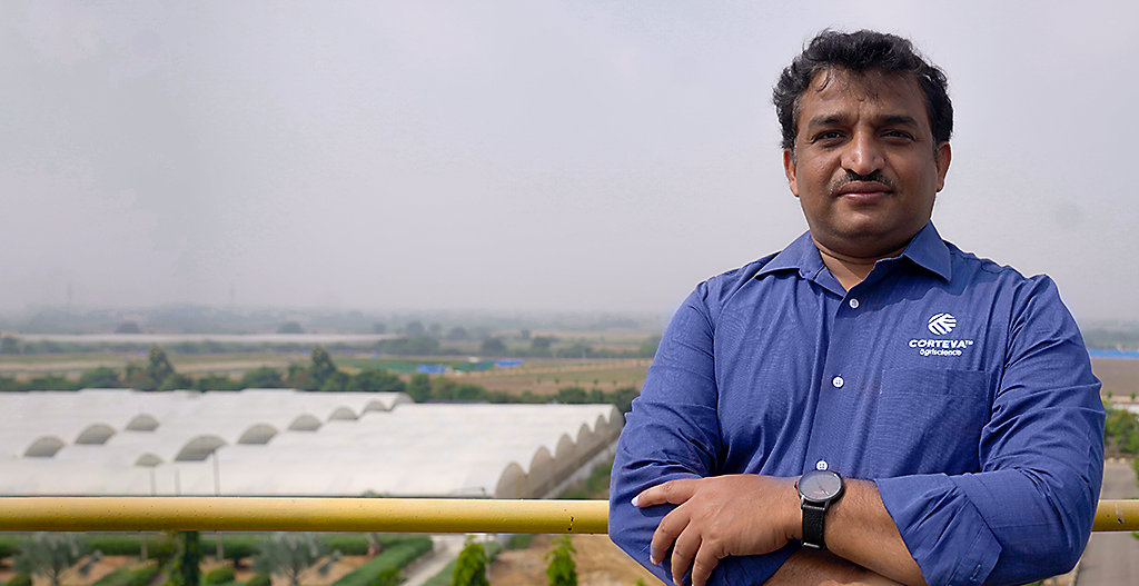 Photo of Corteva research scientist Ramu Punna standing on a rooftop with fields and multiple greenhouse enclosures in the distance. Photo taken at Cortevaâ  s research center in Hyderbad, India.
