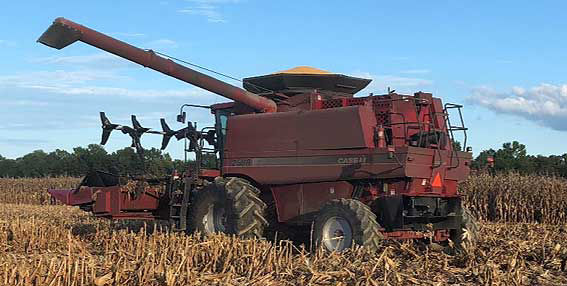 This is a photo showing a combine with aftermarket header reel for harvesting lodged corn.