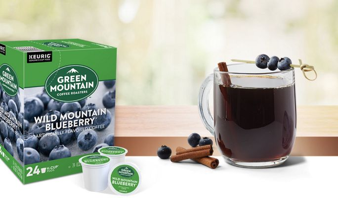Wild Mountain Blueberry K-Cups next to a mug of coffee with blueberries and cinnamon