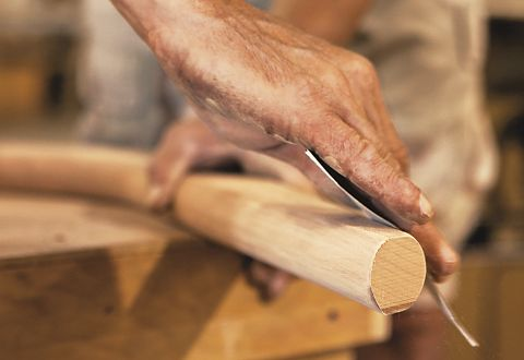 Our products are made by American artisans, like this woodworker shown sanding a chair leg by hand.