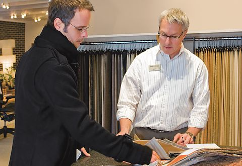 A Design Associate assists a customer with fabric selection