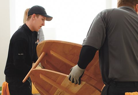 Gloved Room & Board Delivery Associates carefully place a solid wood table in a customer's living room