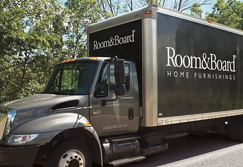 Delivery truck with the Room & Board Home Furnishings logo