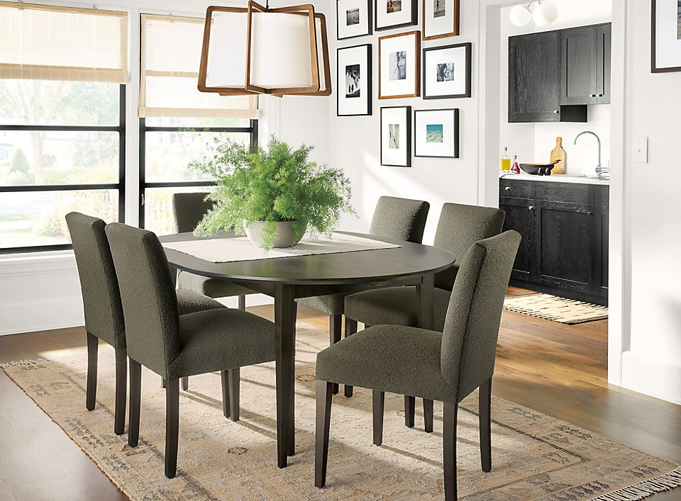 Detail of Adams round extension table in dining room with Peyton chairs and Villa rug