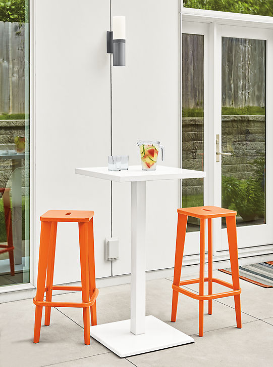 Detail of two Brook bar stools in orange on patio