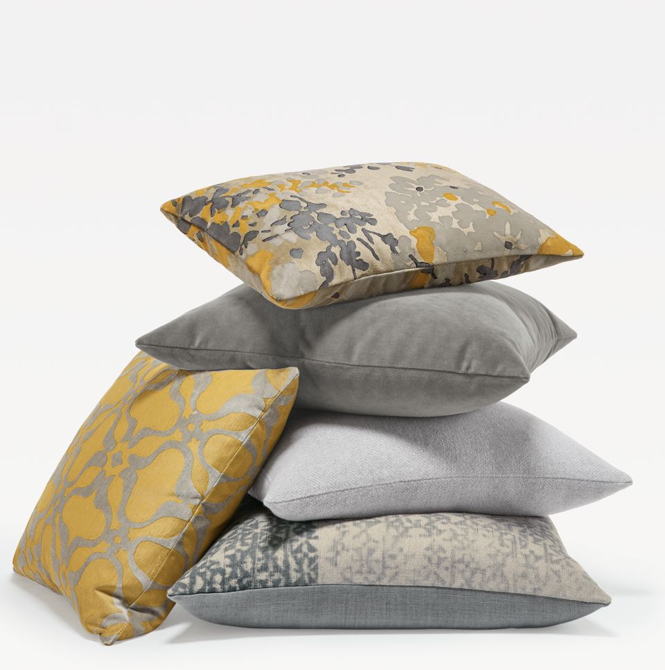 Stack of yellow and silver throw pillows