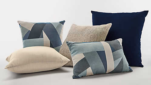 Collection of outdoor pillows in blue and taupe