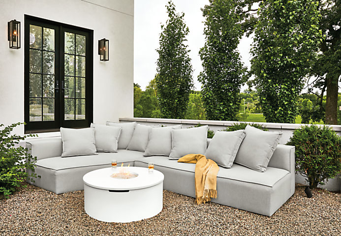 Detail of Oasis outdoor sofa in Mist grey fabric and Adara round fire table in white