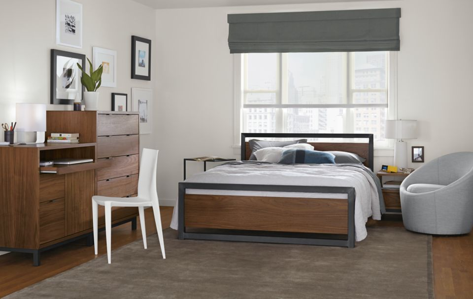 Detail of Piper queen bed in bedroom with walnut panels and natural steel frame
