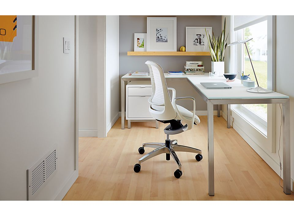 Detail of Portica desk in office with white glass top and stainless steel base