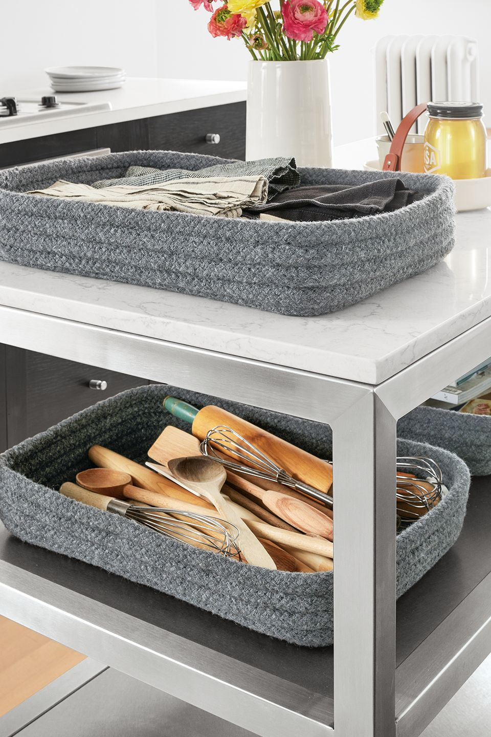 Detail of Portica two-shelf counter table with stainless steel base and marbled white quartz top