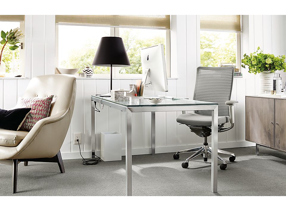 Detail of Portica desk with stainless steel base and clear glass top, and USB and power