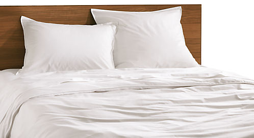 Combination of Sommerville percale full/queen duvet cover in white, Sommerville percale standard sham in white, Sommerville percale euro sham in white, Sommerville percale queen sheet set in white with white stitching and Copenhagen queen bed