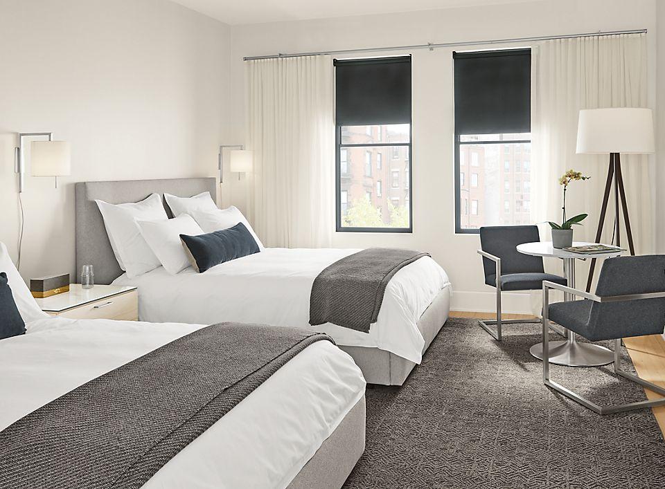 Detail of Wyatt queen beds (2) in Boyer grey fabric in hotel room